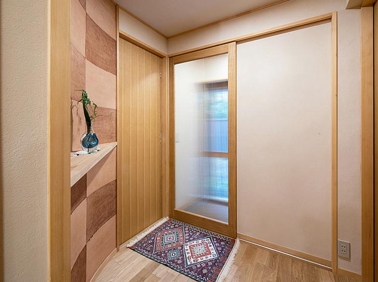 玄関ホール 防寒引戸と曲面の飾り棚