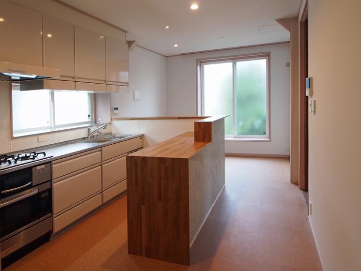 キッチン:造作カウンターを介して奥に食堂コーナー