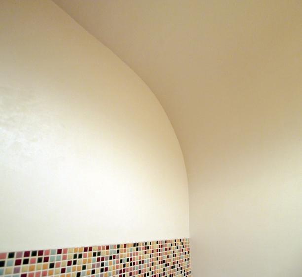 漆喰の壁が円弧を描いて天井に繫がる
