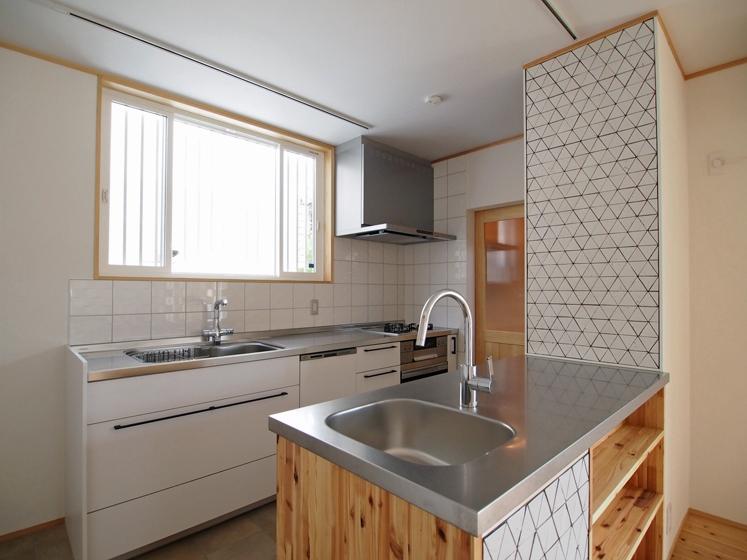 流し付カウンターを設けたキッチン、コンロ脇の扉を引くと洗濯室がある